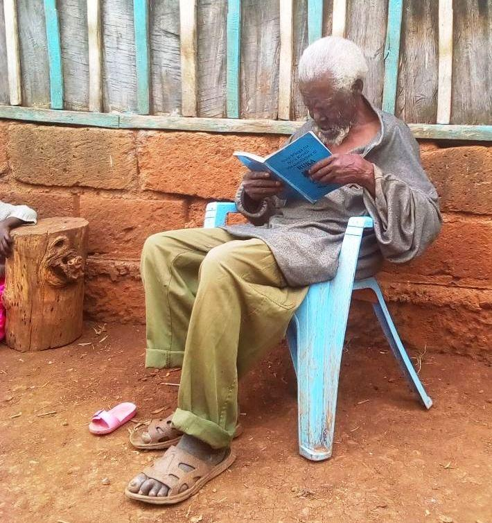 An elderly man in Chuka reading the Bible